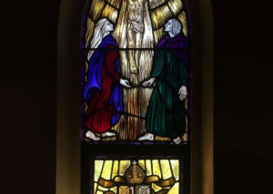stained glass window with jesus in upper arched window and shield in lower window