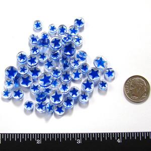 pile of millefiori blue stars on clear pattern on white background